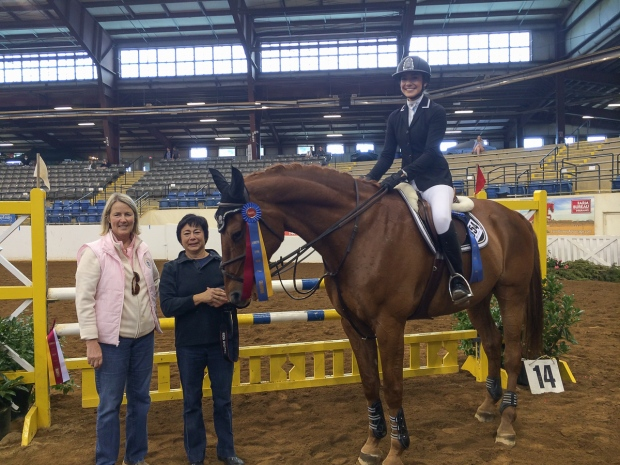 Alex Tippett and El Cano celebrate their High Children's Jumper Championship with, from left, show manager Leslie Brown and mother Michele Tippett